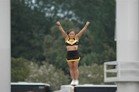 Southern Miss cheerleader standing tall with arms spread