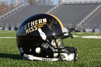 autographed black Southern Miss football helmet in football stadium
