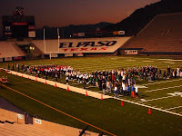 Football team in blue takes the field at dusk with a stadium that reads El Paso Texas in the stands.