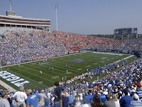 A sold out crowd at a University of Memphis Tigers football game under a blue sky.
