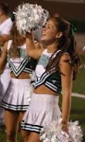 Marshall University cheerleader smiling and raising a white pom pom at a football game.
