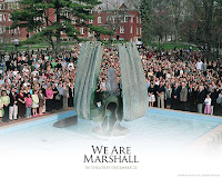 We Are Marshall fountain memorial on the Marshall campus with a crowd of students and faculty surrounding the sculpture.
