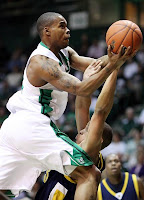 A Marshall University basketball player in a white uniform goes up for a shot over a defender.