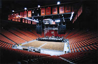 Empty basketball arena with lights dimmed off the court.  Arena filled with orange seats and orange uniforms hanging from the rafters.