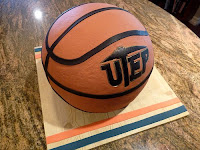 Orange basketball sits on brown desk.  Basketball has the letters UTEP written on the basketball in thick black letters with the letter T being the shape of a miners pick.