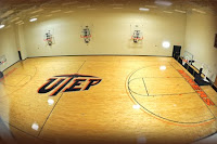 Empty indoor basketball court viewed from above withe center court having the letters UTEP painted in blue and orange at center court.