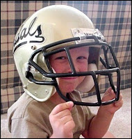 Kid puts on Vandals football helmet.