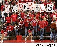 fans at UNLV basketball game hold GO REBELS sign.