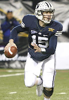 BYU quarterback runs with the ball in a football game.