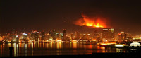 Hillside southern California fire behind San Diego skyline at night.