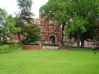 Dark red brick building in a lush area of the Marshall University campus with an abundance of green grass and trees.