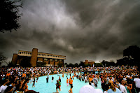 Students flood and overcrowded campus pool under a stormy Orlando, Florida sky.
