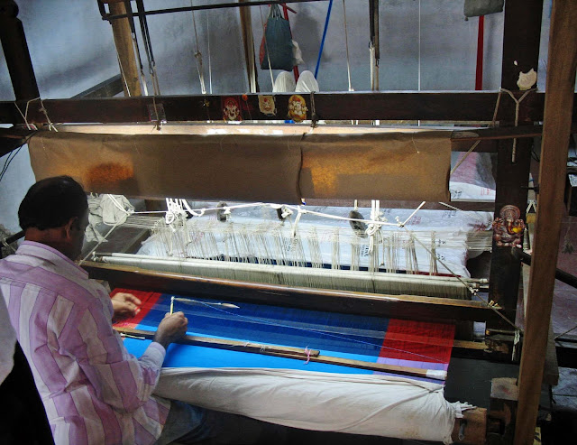 weaver at work on a manual loom
