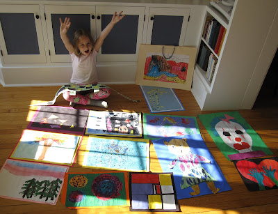 girl surrounded by her kindergarten art