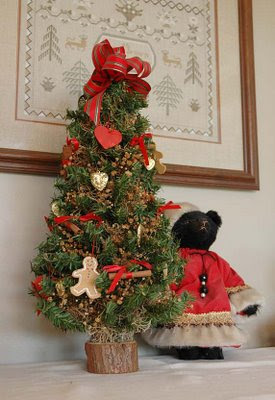 a little black Santa bear cozies up to a rustic tree in the breakfast room