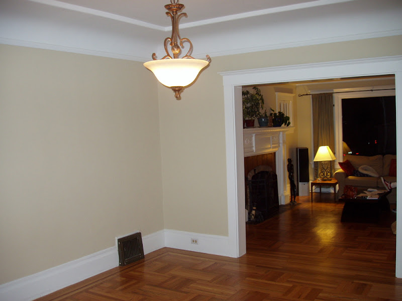 Dining room before Niche Interiors's redesign with outdated ceiling light and beige walls