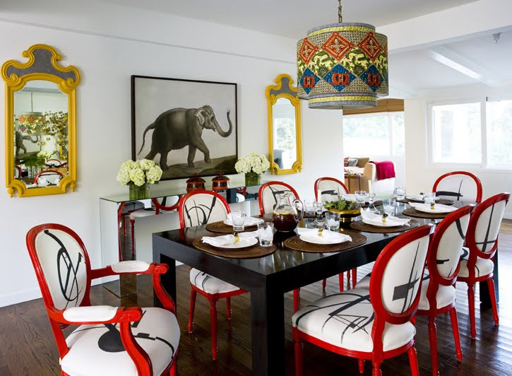Nice-dining-room-with-fantastic-painted-red-and-upholstered-dining-chairs-black-dining-table-and-wall-mirrors