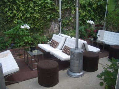 Outdoor patio with white Barcelona inspired chairs and sofa, orchids and metal side tables