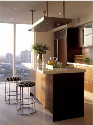 Kitchen by Deborah Wecselman with dark brown wood cabinets, integrated appliances, quartz counter top and modern island lighting