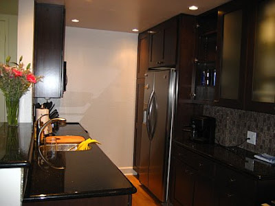 Small kitchen after remodeling with stainless appliances, black counter tops and cabinets