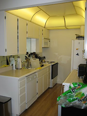 Kitchen before remodeling with white cabinets and counter tops