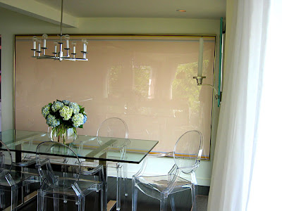 Dining room by M. Design Interiors with a glass table, Philippe Starck Ghost Louis Chairs and a modern chandelier