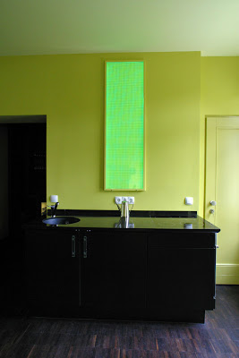 Kitchen with black counters, yellow walls and modern kitchen light