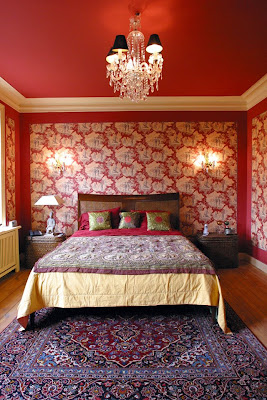 Red bedroom with graphic wallpaper, white crown molding, crystal chandelier and a Turkish rug