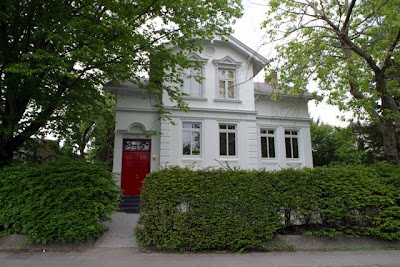 Exterior of a white Hamburg home with a red door