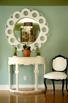 Hand carved and painted round white mirror from Wandrlust in an foyer