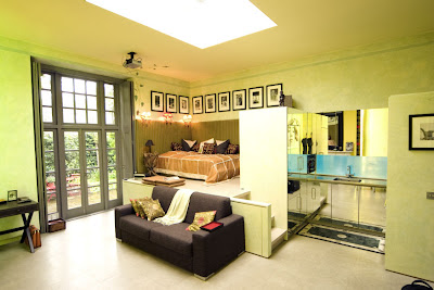 One room flat with living room seating area, bed and storage from built in cabinets and shelving