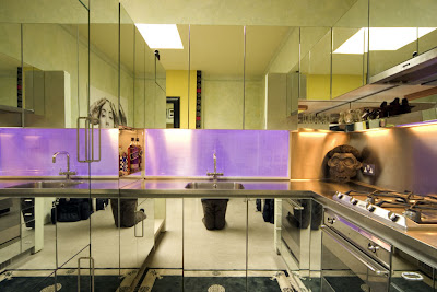 Mirrored kitchen in a London flat with a light feature above the sink that changes colors