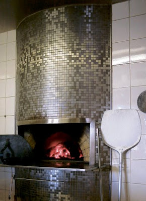 Ann Sacks' stainless steel tile on a fireplace chimney of a modern pizza oven