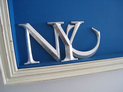 Silver letters in a shadow box made by Shannon Cockrell hung on a wall in her London flat