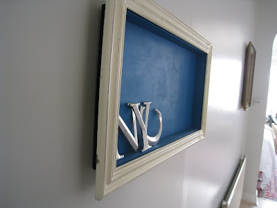 Side view of a shadow box made by Shannon Cockrell hung on a wall in her London flat