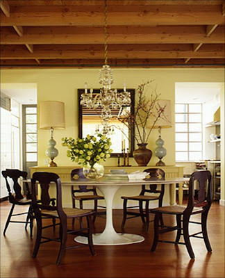 Dining room with retro Saairnen table, dark wood chairs, crystal chandelier and yellow walls