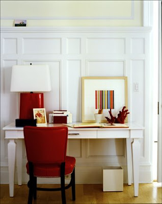 Home office with white paneled walls, white desk, a red leather chair, table lamp and red and black accessories
