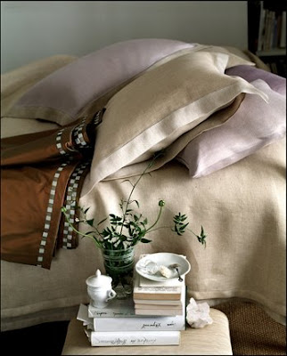 Bedroom with tan and pale purple bedding and a small nightstand
