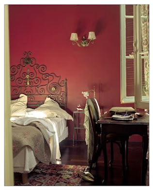 Bedroom with red walls, wrought iron scroll headboard and dark wood desk with matching chair
