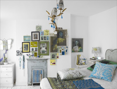 White bedroom with blue and green accents and a collage of framed pictures on a fireplace mantel
