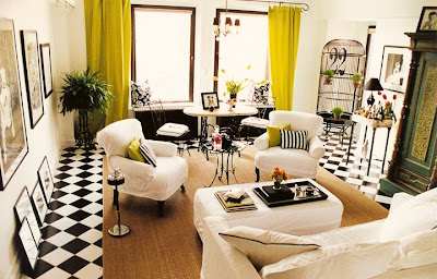 Living room by Jeff Andrews Design with black and white checker board tile floor, white walls, grand black paned windows with chartreuse curtains and white slipcovered armchairs and sofa