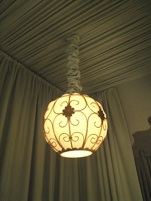 Round and iron pendant lights hang from each canopy in a guest bedroom in the Greystone Mansion