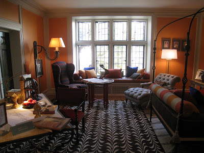 Gentleman's bedroom in the Greystone Mansion with bright orange walls and patterned rugs by James Lumsden