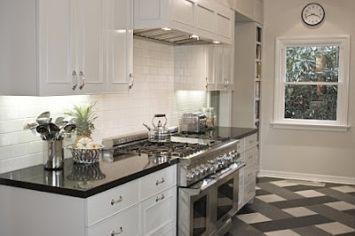 Crisp white kitchen glass-front cabinets and shiny black granite
