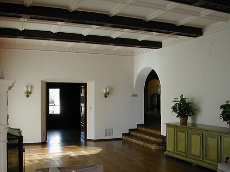 Living room before remodeling with hardwood floor, arched door, and a beamed and paneled ceiling