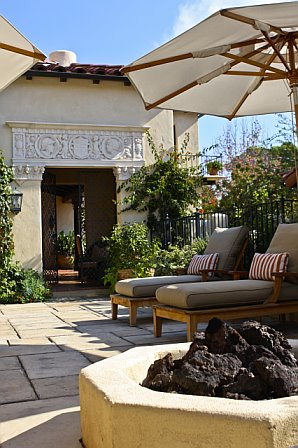 Auto court entry is turned into a poolside lounge space with a fire pit after remodeling
