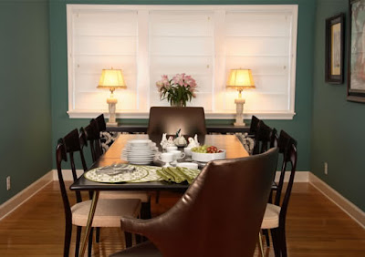 Dark teal dining room with brown leather host chairs, black high gloss wood side chairs and a simple black dining table with metal legs