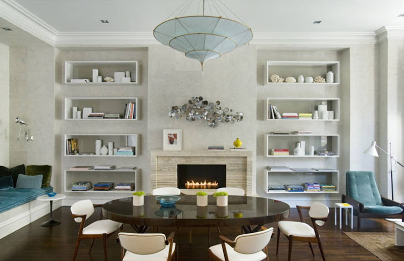 Grey dining room with white shadow box shelving, dark brown round wood table surrounded by retro white leather and wood chairs, a blue umbrella style chandelier and velvet cushion on a window seat and a silver 1950s inspired wall sculpture over the fireplace mantel