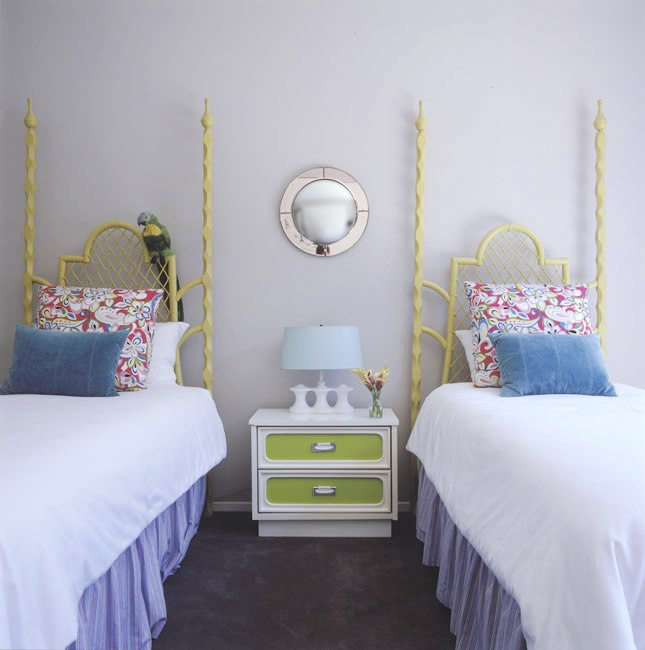 Children's bedroom with two twin beds with lime green spindle headboards, light purple walls, carpeted floor and a white nightstand with lime green drawers