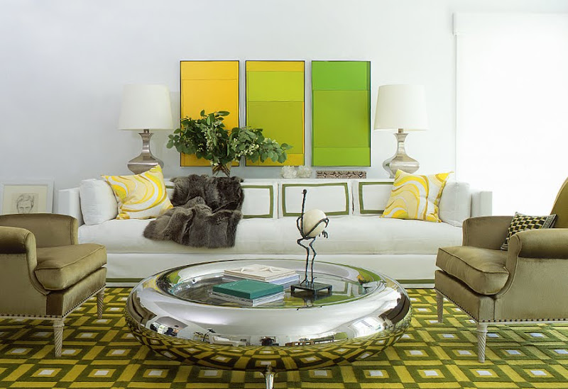 Modern living room with green dueling armchairs, a chrome donut-like coffee table, graphic green rug and a white sofa with green and yellow accent pillows